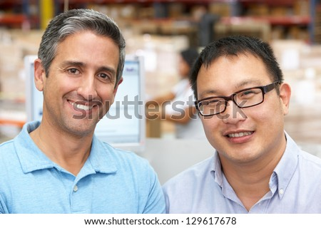 Two Men At Computer Terminal In Distribution Warehouse - stock photo