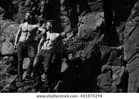 Two men athletic male twins with bare torso in jeans show muscular body abs on rocks black and white on mountain background - stock photo