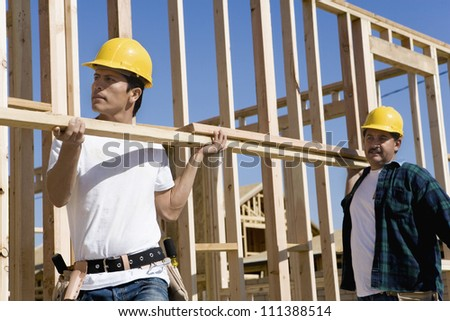 Two men carrying wooden timber at a construction site - stock photo