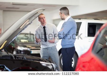 Two men chatting in front of an open engine in a car dealership