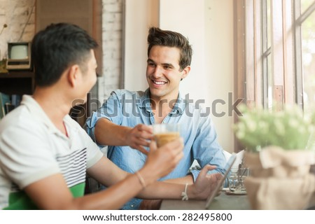 Two Men Cheers Toast Drink Friends Guys Happy Smile Sitting at Cafe Natural Light - stock photo