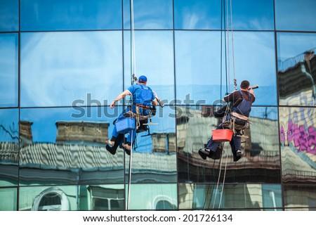 Two men cleaning window facade of skyscraper - stock photo