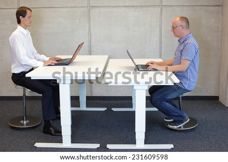 two men  coworking in correct sitting posture on pneumatic leaning seats  with laptops  at electric height adjustable desks in office - stock photo