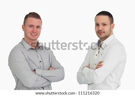 Two men crossing arms and standing side by side against a white background - stock photo