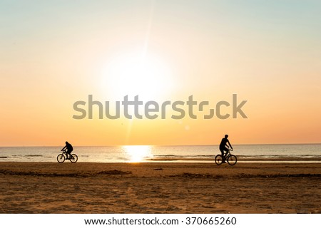 Two men cyclists silhouettes at summertime sunset background on the beach. Summertime multicolored outdoors horizontal image - stock photo