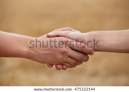 Two men, farmers shake his hand against the background of the field.