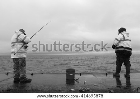Two men fishing and putting the fish in a bucket - stock photo