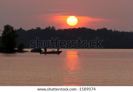 Two men fishing on a remote Wisconsin lake at sunset. - stock photo