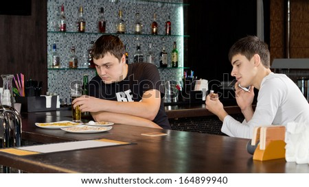 Two men friends enjoying themselves having a drink of beer at the bar with one busy having a conversation on his mobile phone - stock photo