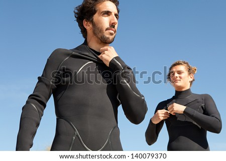 Two men friends getting dressed and ready with their surfing neoprene waterproof suits on a beach with an intense blue sky in the background during a sunny day. - stock photo