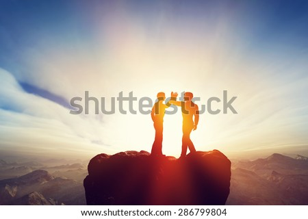Two men, friends high five on top of the mountains. Agreement, positive energy, friendship concepts. Sunset sun light.  - stock photo