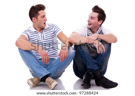 two men friends looking one at the other while sitting next to each other on white background. they both look very surprised - stock photo