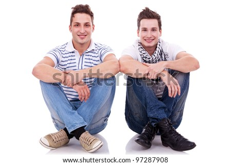 two men friends looking very happy, sitting next to each other on white background - stock photo