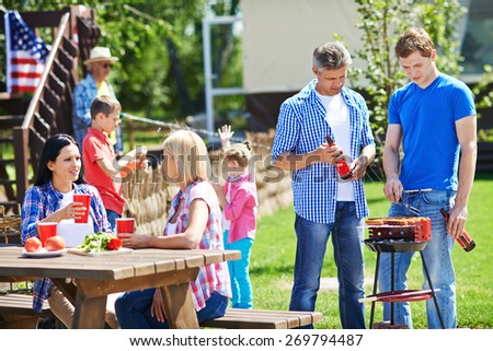 Two men frying sausages on grill outdoors with young women talking by table near by