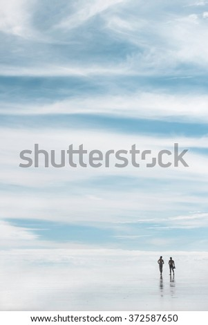 Two men go on the beach against the sky . Reflections in the water . Perspective . Beautiful sky . Happy people walking in the clouds on the beach. Travel. - stock photo