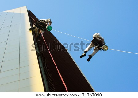 Two men hanging high on a rope while working - stock photo
