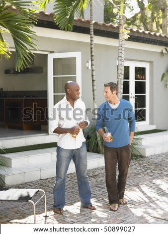 Two men having conversation on patio - stock photo