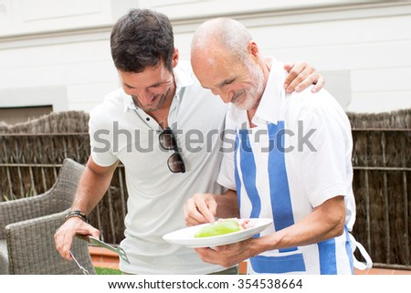 Two men having fun during barbecue - stock photo