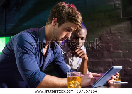 Two men having whiskey and using digital tablet at bar counter in bar - stock photo