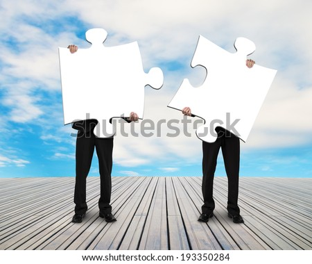two men holding puzzles on wooden floor outside with blue sky - stock photo
