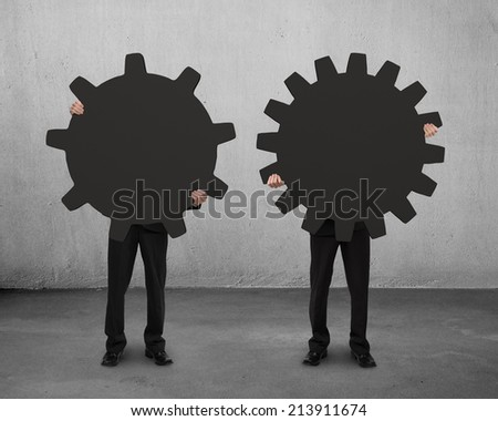 two men holding their different gear on concrete floor with cement wall - stock photo