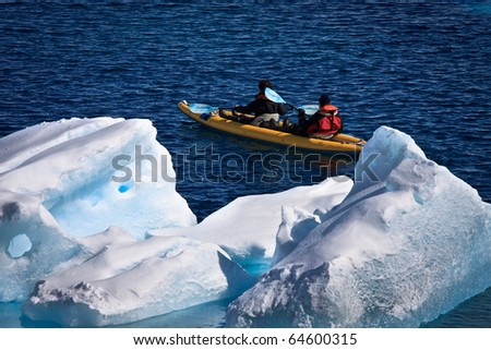 Two men in a canoe among icebergs in Antarctica - stock photo