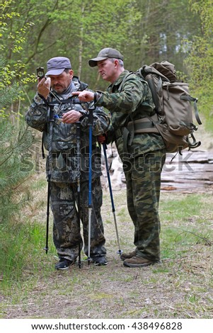 Two men in camouflage uniforms and backpacks to define your way across the map using a compass.