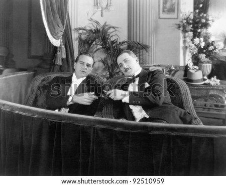 Two men in formal attire sitting together in a theater box - stock photo