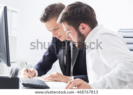 Two men in formal clothes working together. First is taking notes. Second looking at results. Concept of collaboration