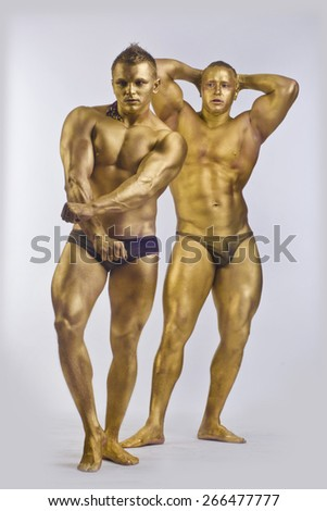Two men in gold paint athletic indoors