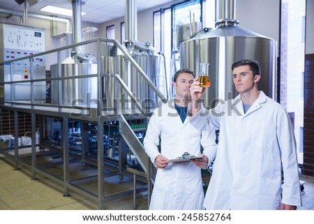 Two men in lab coat looking at the beaker with beer in the factory - stock photo