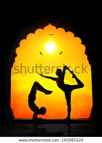 Two men in silhouette doing yoga difficult poses in old temple at orange sunset sky background - stock photo