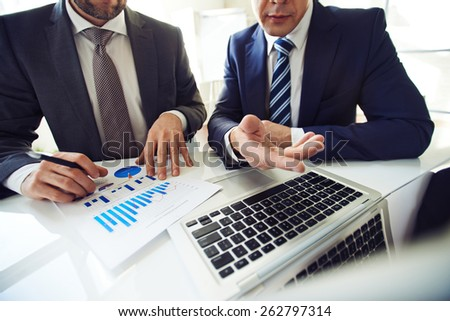 Two men in suits searching for decision in financial issues - stock photo