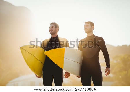 Two men in wetsuits with a surfboard on a sunny day at the beach - stock photo