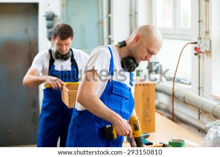 two men in work-wear in a carpenter's workshop - stock photo