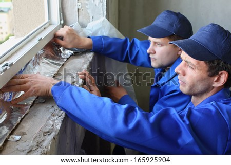 Two men in working clothes places the foiled insulation on the window sill - stock photo