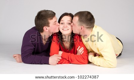 Two men kissing a young girl between them