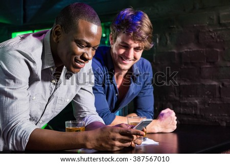 Two men looking at mobile phone and smiling while having whiskey at bar counter in bar - stock photo