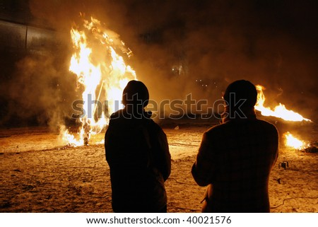 Two men looking at the fire - stock photo
