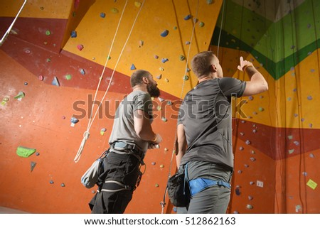 two men  on climbing gym, discuss the route.