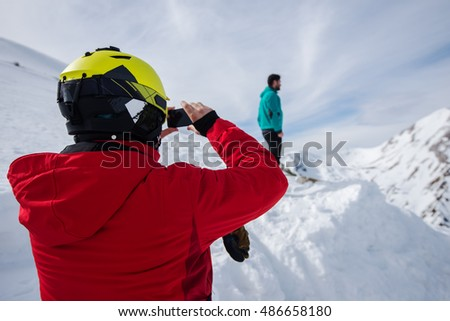 Two men on the top of a snowy mountain, taking pictures.