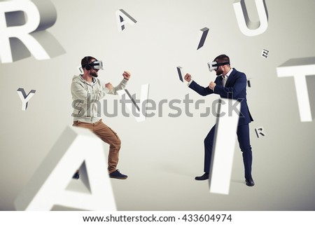 Two men, one in casual clothes, another in dark business suit, are wearing virtual reality glasses and standing in fighting poses ready to start their combat in virtual reality  - stock photo