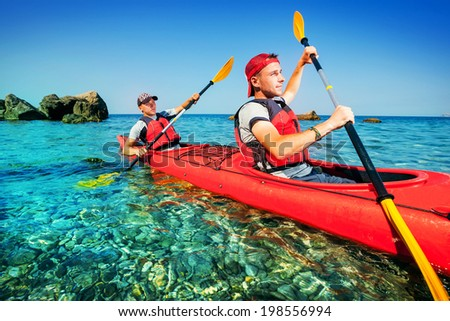 Two men paddle a kayak on the sea. Kayaking on island
