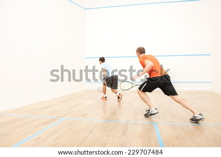 Two men playing match of squash. Back view of squash player in action reaching on squash court  - stock photo