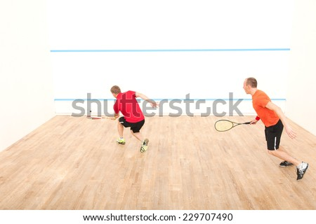 Two men playing match of squash. Back view of squash player in action reaching on squash court