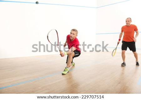 Two men playing match of squash. Closeup of squash ball in action on squash court  - stock photo