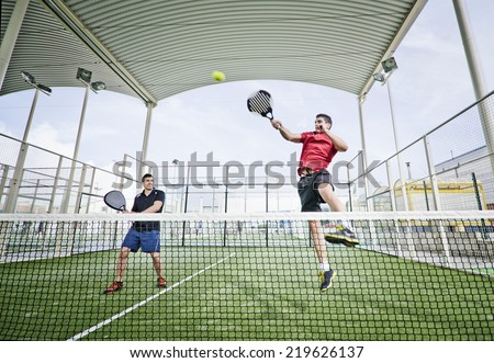 Two men playing paddle tennis in wide angle shot image