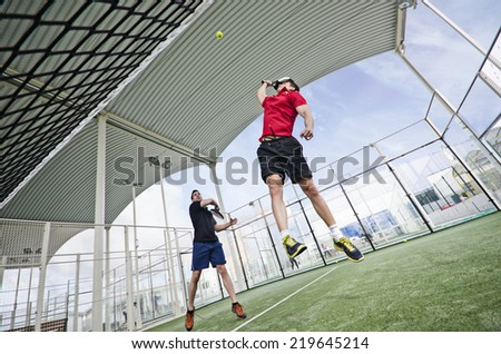 Two men playing paddle tennis in wide angle shot image - stock photo