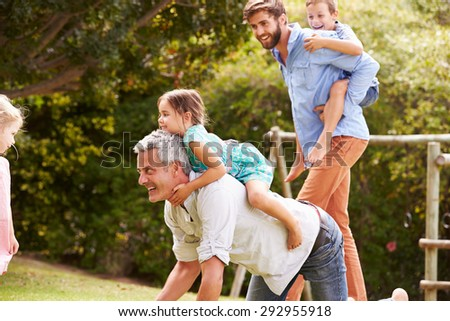 Two men playing with kids in a garden - stock photo