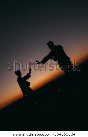 Two Men Practising Wushu at Sunset - stock photo
